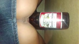 Slut inserting beer bottle in her pussy